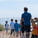 Children and adults walking in a line next to the bay