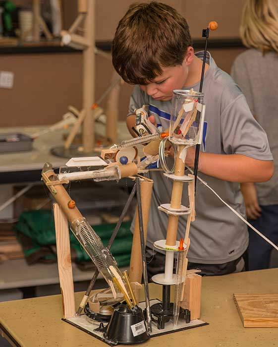 Boy building marble rollercoaster
