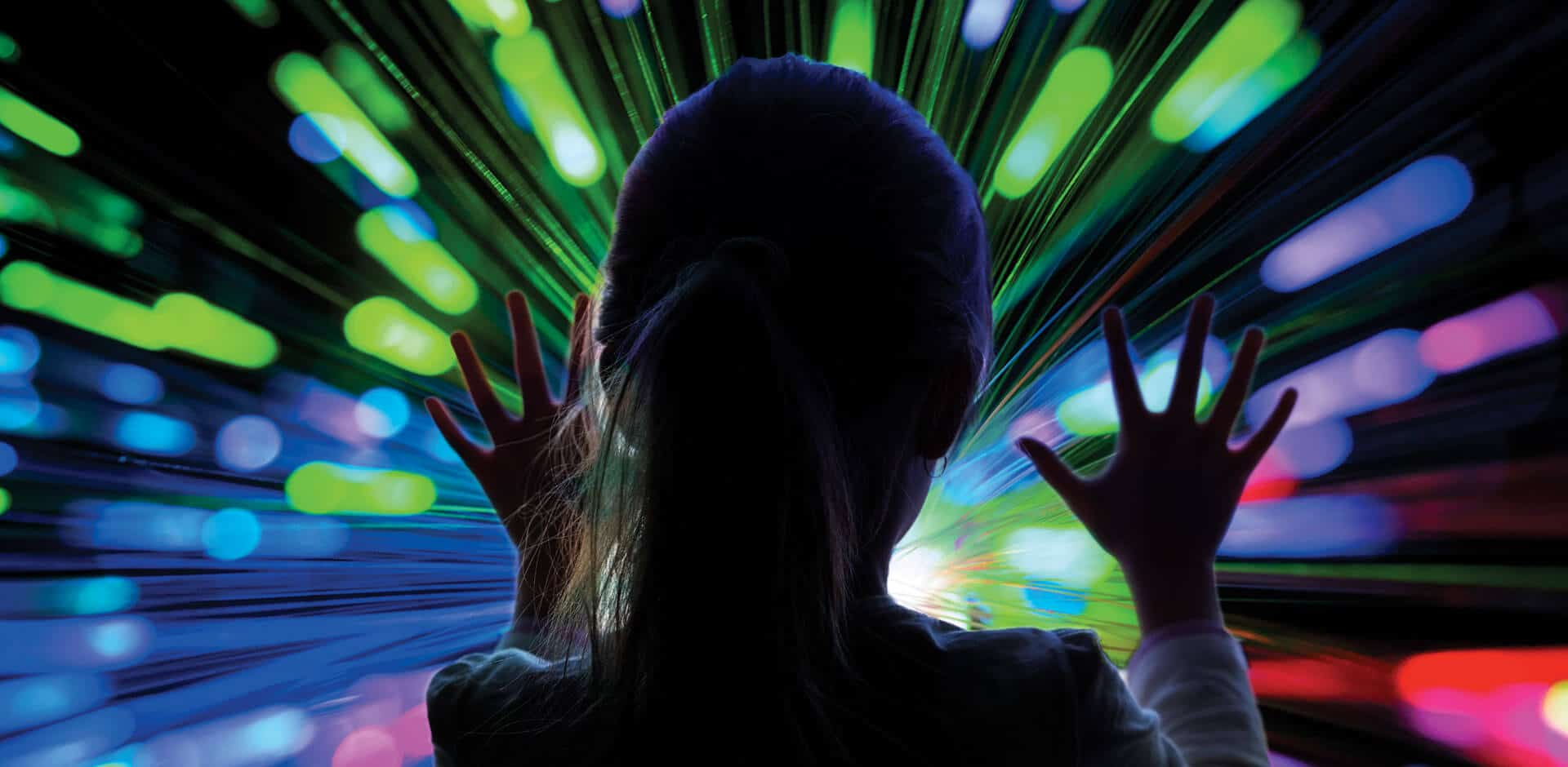 Girl reaches up toward colored lights