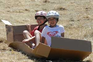 Two kids slide down hill on cardboard slide