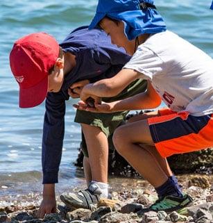 Two children explore a rocky beach