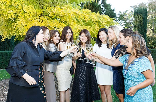 Gala guests form half circle and hold up champagne glasses in a toast
