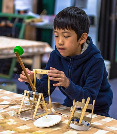 A boy makes a catapult to learn about the physics principle of stored energy.