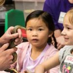 Children face small snake in classroom