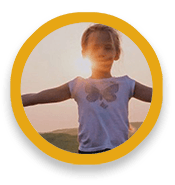 Child with arms outstretched to side, with sun behind