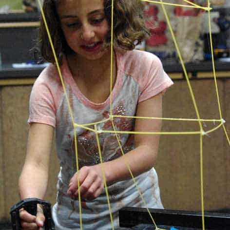 Girl simulates earthquake with building model