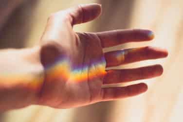 Rainbow light shines on open hand.