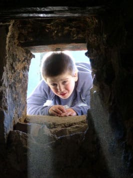 Child peers through one end of a tunnel formed by rocks.