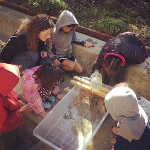 Young children join an educator in observing the process of erosion via a box of sand and water falling from a source. The grant to CuriOdyssey will support education efforts like this.