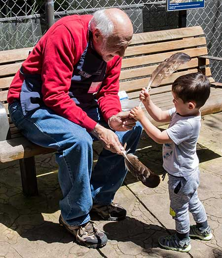 Volunteer shows bird feather to young visitor