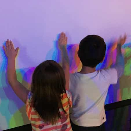 Children touching shadows on a wall