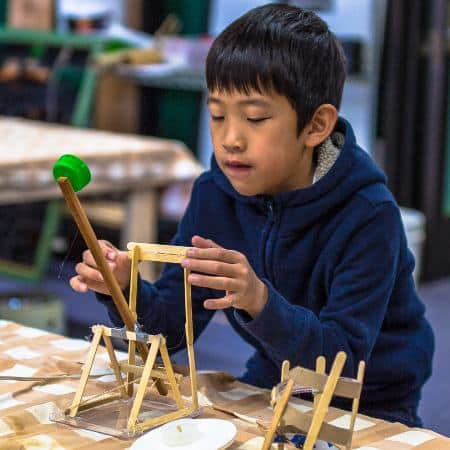 image of a boy building a toy catapult