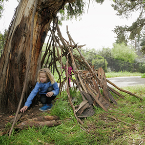 Child building a fort from tree bark