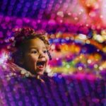 Child laughing, surrounded by colored lights