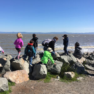 Children climbing over rocks on bayside jetty