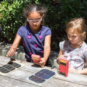 Two children sit at picnic table with solar meters